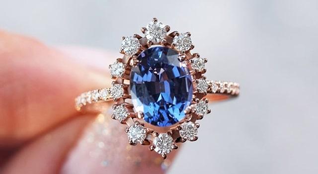 Blue Tanzanite engagement ring with diamonds surrounding and diamond band