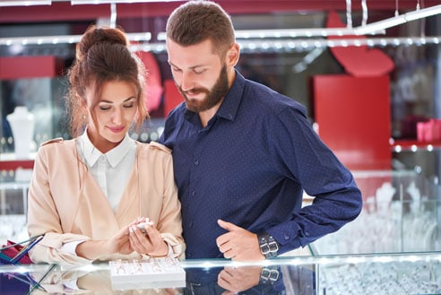 A Man and Woman shopping for an engagement ring in a jewelry store